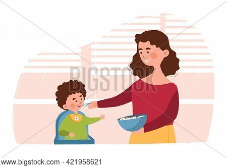 Young Mother Is Feeding Her Little Son In High Chair In The Kitchen. Mom Is Feeding From A Bowl In H