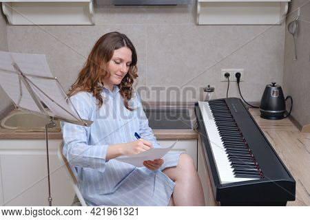 Woman Composer In A Nightgown Writes Sheet Music On A Piece Of Paper. Writing Music At Home With A D