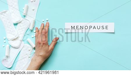 Menopause Word On Blue Background. Woman Hand Pushes Aside Menstrual Pads, Tampons And Contraceptive