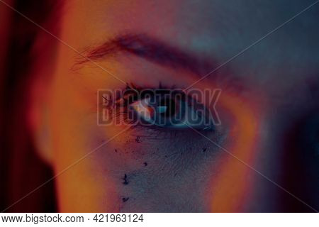 Close-up Of A Female Eye With Neon Light Flowing Mascara On Her Face After Tears.
