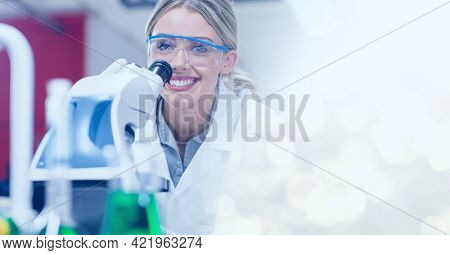 Composition of smiling female lab technicians using microscope, with white bokeh copy space to right. medical and science research concept digitally generated image.