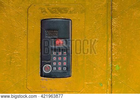 An Intercom On Old Painted Yellow Steel Surface With A Keypad, Digital Display And Rfid Sensor For C