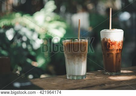 Glass Of Iced Latte Coffee And Iced Mocha Placed On Wood Table With Garden Background At Outdoor Caf