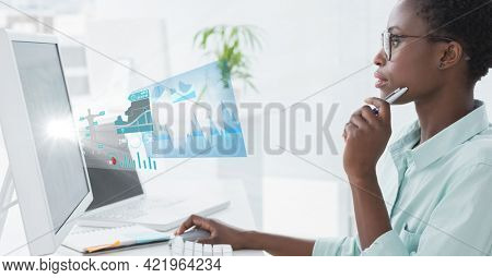 Composition of woman sitting at desk using computer with medical research data interface screen. global medicine, research and digital interface concept digitally generated image.