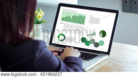 Composition of person at desk using laptop, with research data interface screen. global research, communication and digital interface concept digitally generated image.