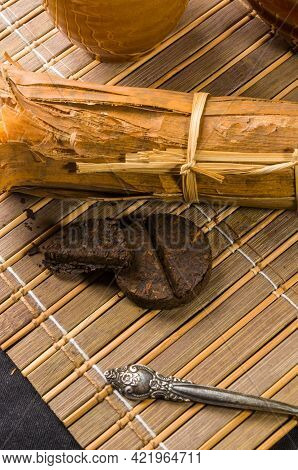 Chinese Pressed Pu-erh Tea In Bamboo Leaf Packaging And Tea Accessories On A Bamboo Mat, Close-up, M