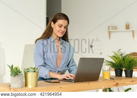 Happy Smiling Young Woman Sitting At A Desk At Home, Working In A Laptop Or Spending Time On Distanc