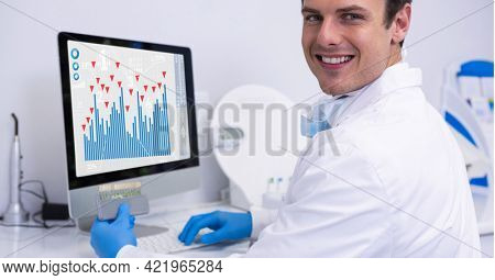 Composition of smiling male doctor using computer with medical research data interface on screen. global medicine, research and digital interface concept digitally generated image.