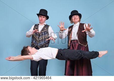 Magicians Levitated A Boy In The Air, Circus Performers On A Blue Background