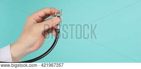 Close Up Of Doctor Hand Holding Stethoscope And Wear Long Sleeve Gown On Mint Green Or Tiffany Blue
