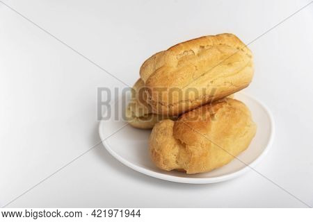 Profiteroles Or Eclairs Without Cream On White Saucer. White Background. Homemade Baking.