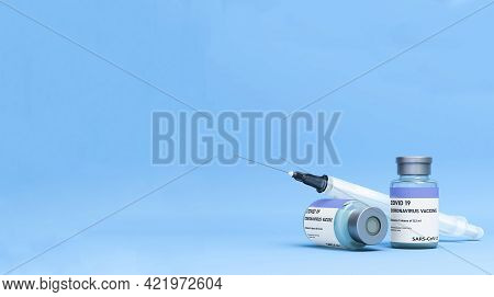 Covid Vaccine Bottle With Syringe On A Light Blue Background
