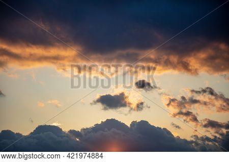 Sunbeams Through Dark Clouds On Blue Sky Background.