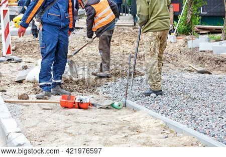 Road Workers Use Shovels To Prepare A Sandy Foundation On A Sidewalk And Cover It With Rubble Along