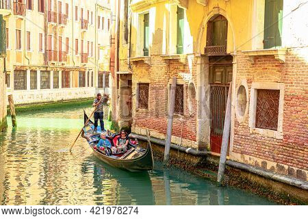 Venice, Italy - May 9, 2021: Close Up On Traditional Boats And Gondoliers On Canals Of Venice Throug