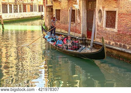 Venice, Italy - May 9, 2021: Traditional Gondoliers In Venice Taking Tourists On Tour On Historic Gr