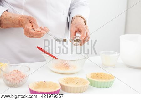 Senior Woman Preparing The Filling For A Delicious Cheese And Ham Tartlet