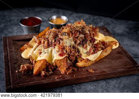 Delicious Gajo Fries Served With Bacon, Jack Cheese, Cheddar Cheese And Bacon On A Rustic Style Boar