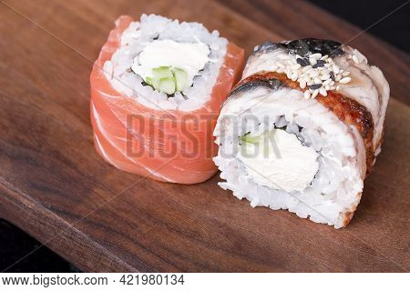 Delicious Fresh Rolls With Red Fish, Awakad, Cream Cheese, Lettuce, Sesame Seeds, On A Wooden Worthy
