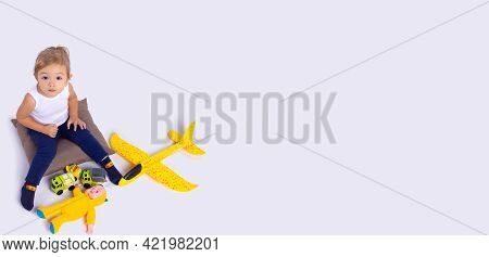 Banner, Long Format On Grey Background. Pretty Kid Looking Up At Camera. Toddler Girl Sitting On Pil