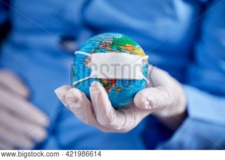 doctor holding globe with protective mask