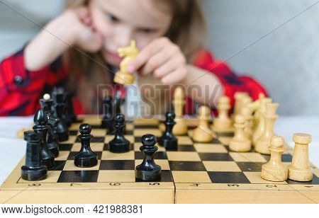 International Chess Day. A Little Girl Learns Chess Pieces And Learns To Play Chess.table Games. Fam