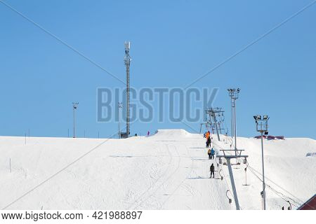 Ski Resort, Gentle Snow Slope With People On The Lift Going To The Top. Mountain Slope For Skiing An