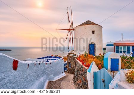 Old traditional whitewashed greek windmill on Santorini island in Oia town with stairs in street. Oia village, Santorini, Greece