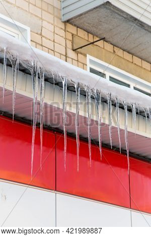 Long Icicles Hang Dangerously Overhanging From The Roof. The Wall Of The Building Is Finished With R