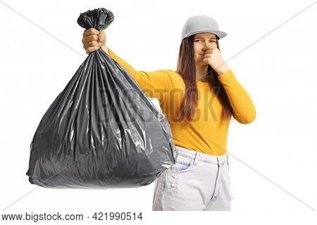 Young female holding a smelly bin bag isolated on white background