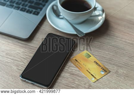 Credit Card Of Laptop Computer, Smartphone Gray Black Empty Screen And Coffee Cup On Wooden Backgrou