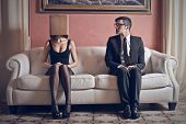 man looks at beautiful woman with box on his head sitting on the couch poster
