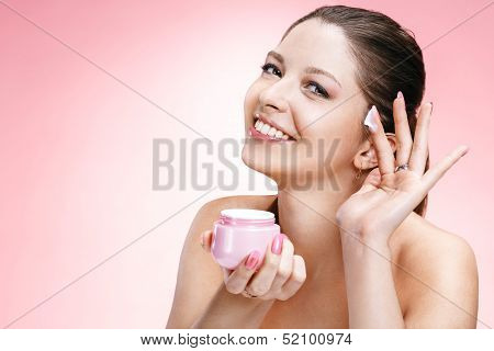 Young beautiful woman with cosmetic cream