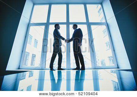 Photo of successful businessmen handshaking after striking deal