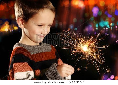 Young boy holding burning sparkler on festive lights background