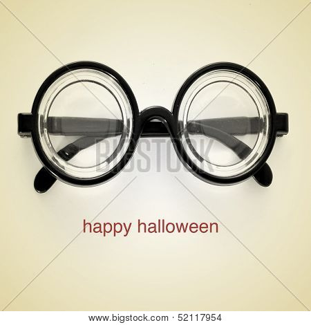 picture of short-sighted glasses and the sentence happy halloween on a beige background, with a retro effect