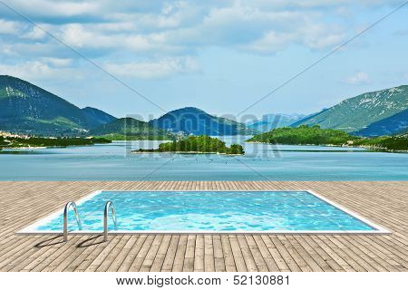 Wooden deck with swimming pool with beautiful view of sea and mountains