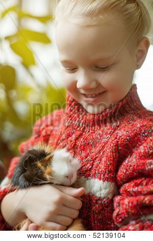 Portrait of smiling little girl looking at cavy