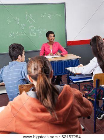 Young African American female teacher and teenage students sitting in classroom