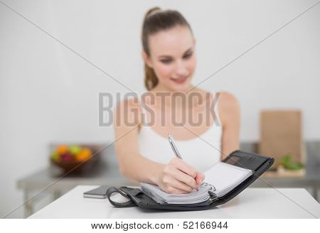 Smiling young woman writing in a planner in the kitchen at home