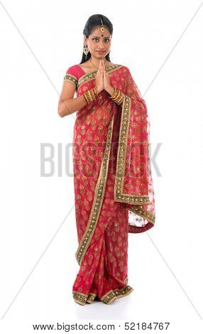Indian girl in a greeting pose, traditional sari costume, full length standing isolated on white background