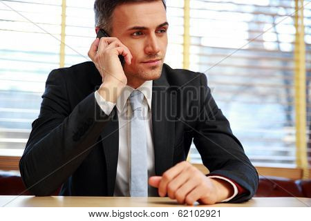 Confident businessman sitting and talking on the phone at office