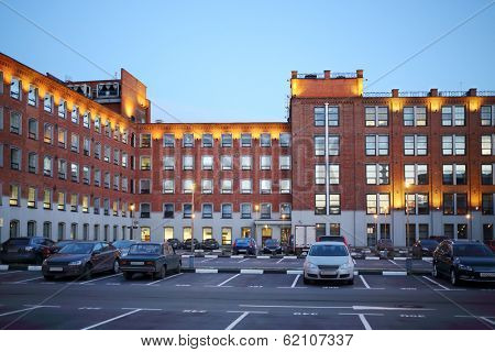 Car parking in courtyard of building built of red bricks at evening