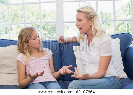 Angry mother scolding daughter while sitting on sofa at home