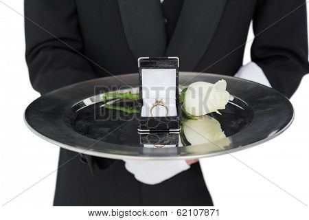Mid section of waiter presenting engagement ring and rose isolated over white background