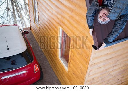 Man holds on the roof of a wooden house with a red car in yard