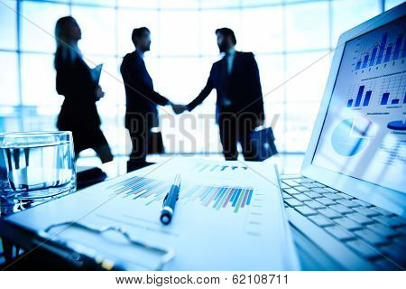 Laptop, financial document with pen and glass of water at workplace on background of three business partners making a deal