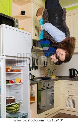 Mother with son stand upside down in the kitchen with fridge