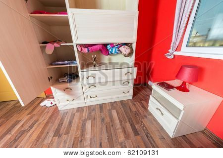 Girl lying upside down in the closet at inverted house