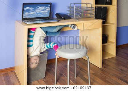 Little girl in jeans under the table with head in basket at inverted house